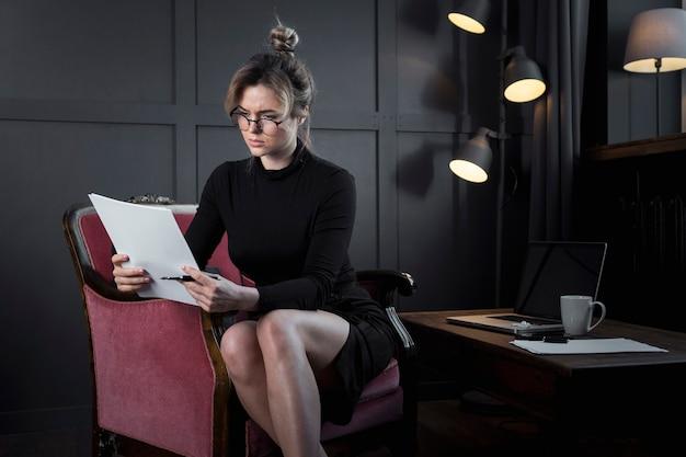 Professionelle geschäftsfrau, die in papiere schaut