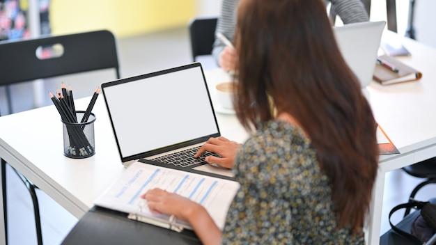 Professionelle geschäftsfrau, die mit versicherungsbericht arbeitet und im büro auf der laptop-tastatur tippt
