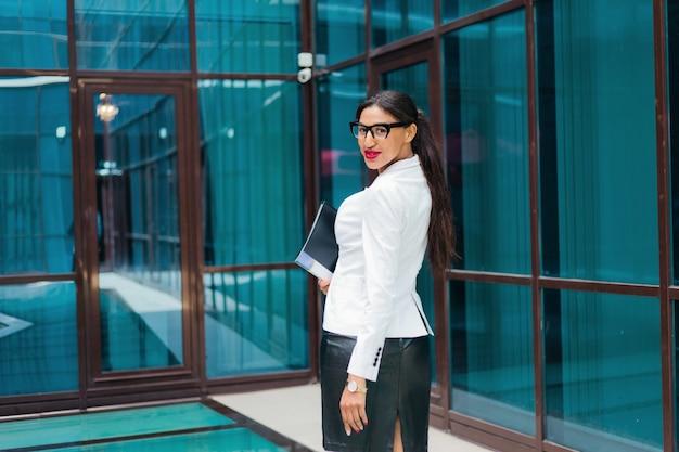 Professionelle geschäftsfrau in eleganter weißer jacke und rock mit ordner mit dokumenten in ihren händen