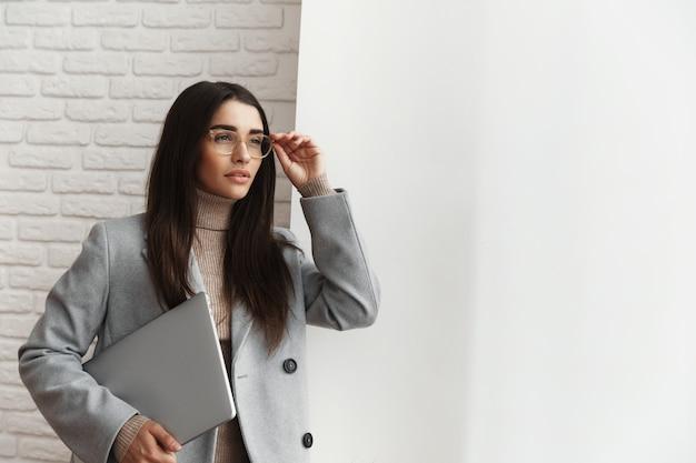 Professionelle geschäftsfrau in gläsern, die nahe am fenster mit einem laptop stehen.