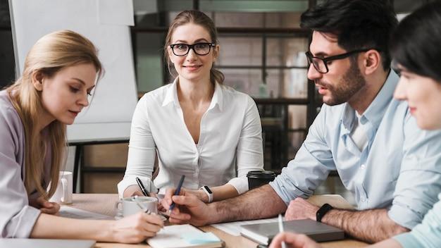 Professionelle geschäftsfrau mit brille während eines treffens mit ihren mitarbeitern