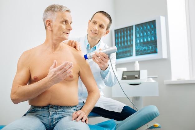 Professionelle gesundheitsversorgung. angenehmer netter alter mann, der in der arztpraxis sitzt und mit seinem therapeuten spricht, während er von ihm untersucht wird
