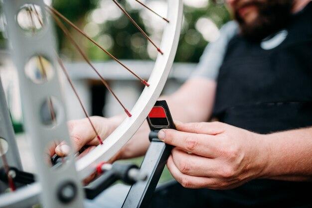 Professionelle hände eines fahrradmechanikers stellen die fahrradspeichen und das reparaturrad mit der nahaufnahme des servicewerkzeugs ein.