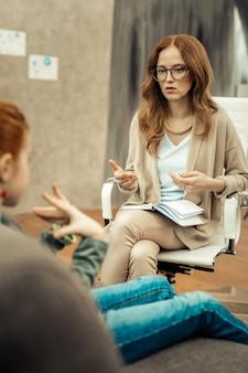 Professionelle hilfe. positive gutaussehende frau, die ihre notizen hält, während sie mit ihrem patienten zusammensitzt