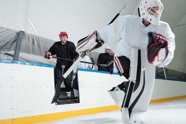Professionelle hockeyspieler in sportuniform, helmen, handschuhen und schlittschuhen gehen auf die eisbahn, um im großen stadion zu spielen, während sie stöcke halten