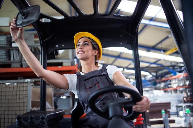 Professionelle industriefahrerin, die die rückspiegel einstellt und die gabelstaplermaschine im fabriklager bedient