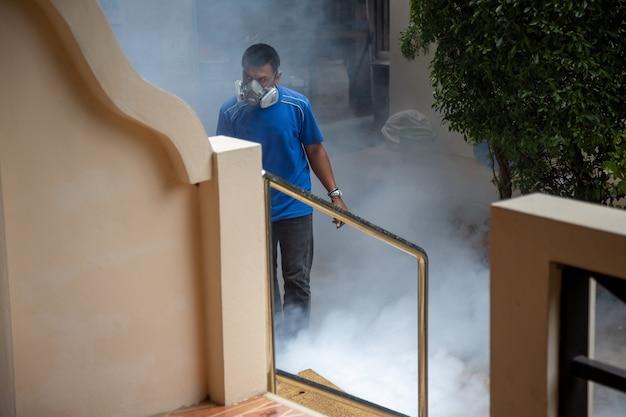Professionelle insektenbehandlung. mann mit atemschutzgerät versprüht rauchgift.