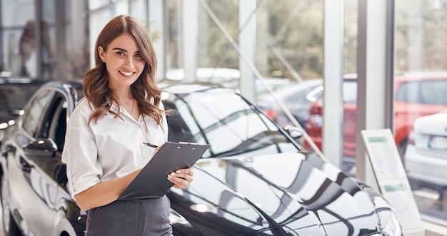 Professionelle junge händlerin mit zwischenablage lächelnd und kamerafreundlich betrachtend, während sie in der nähe des modernen automobils im autohaus steht