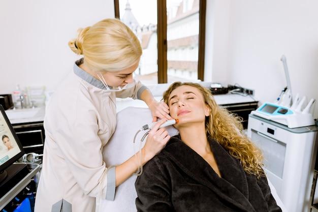 Professionelle junge kosmetikerin, die ein hydrafacial-verfahren in einer kosmetikklinik unter verwendung eines hydra-staubsaugers durchführt.
