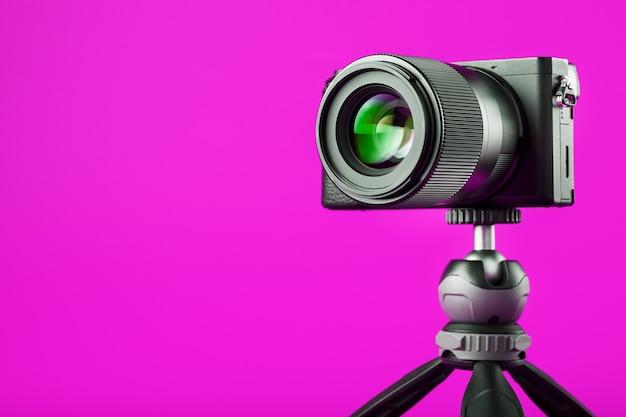 Professionelle kamera auf einem stativ, auf einem rosa hintergrund. nehmen sie videos und fotos für ihr blog oder ihren bericht auf.