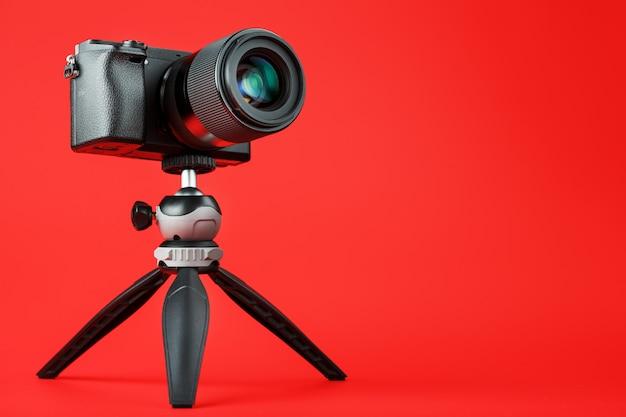 Professionelle kamera auf einem stativ, auf einem roten hintergrund. nehmen sie videos und fotos für ihr blog und ihre reportage auf