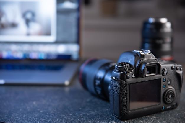 Professionelle kamera auf einem unscharfen hintergrund mit einem laptop. das konzept der arbeit mit fotos und videos.