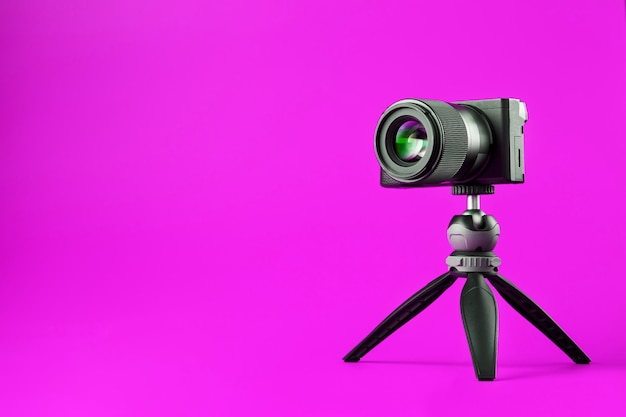 Professionelle kamera auf stativ, auf pink. nehmen sie videos und fotos für ihr blog oder ihren bericht auf.