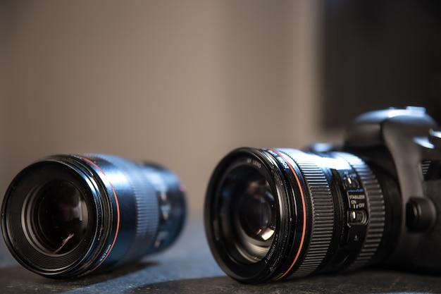 Professionelle kamera-nahaufnahme auf dem desktop eines fotografen auf einem unscharfen hintergrund
