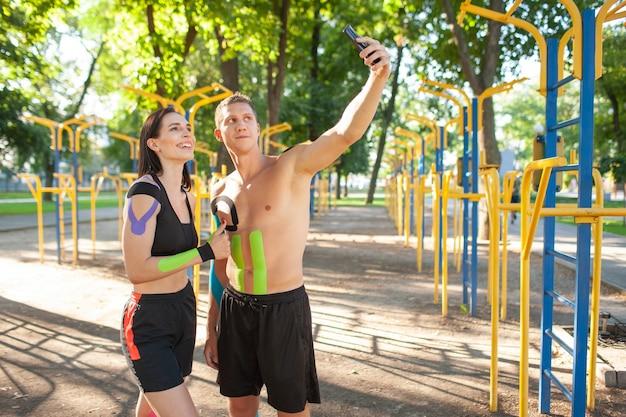 Professionelle kaukasische athleten mit kinesiologischem elastischem taping auf körpern, gutaussehender mann und brünette frau, die auf sportplatz aufwerfen, sich ausruhen und selfie mit smartphone nehmen.