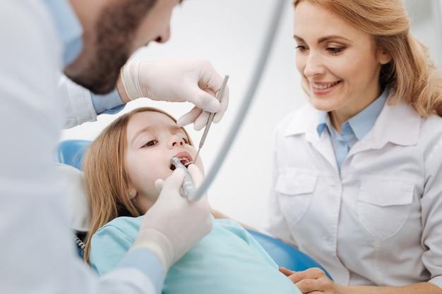 Professionelle, kompetente medizinische kollegen, die kleine patientenzähne untersuchen und eine routineuntersuchung durchführen, während sein kollege sie tröstet