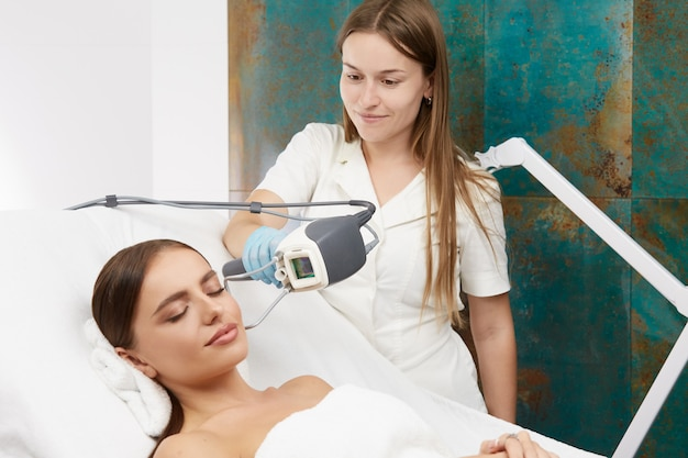 Professionelle kosmetikerin, die laser nahe frauengesicht im spa-salon hält