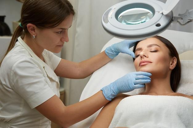 Professionelle kosmetikerin, die mit schönem frauengesicht in blauen handschuhen an der hautklinik arbeitet