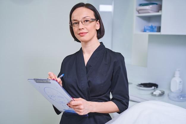Professionelle kosmetikerin. freundliche kosmetikerin, die ein lächeln auf dem gesicht hält, während sie sich während der beratung notizen macht