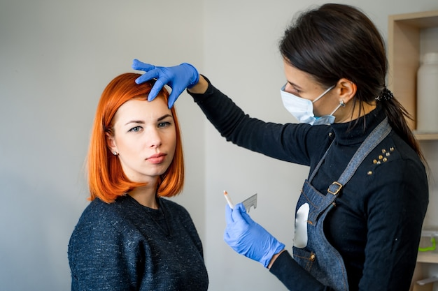 Professionelle kosmetikerin hinterlässt spuren im gesicht des kunden. augenbrauen tätowieren, permanent make-up