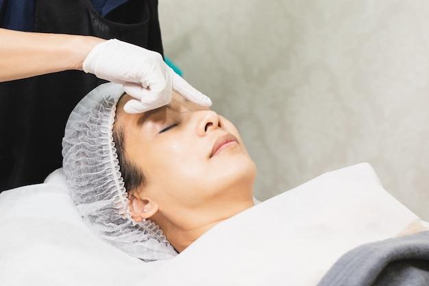 Professionelle kosmetikerin mit ölpipette trägt serum auf das gesicht des kunden auf.