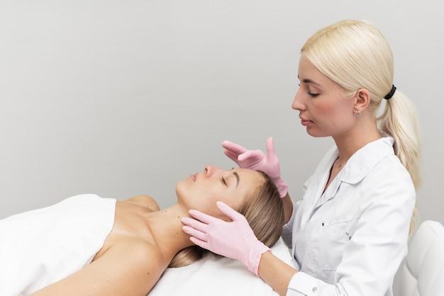 Professionelle kosmetikerin trägt weiße kosmetikcreme auf ein mädchen auf, das in einem modernen spa auf einer couch liegt
