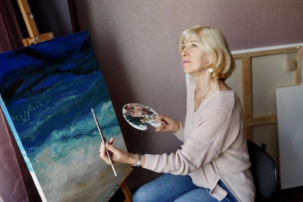 Professionelle künstlerin, die auf leinwand malt