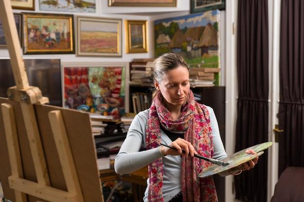 Professionelle künstlerin, die bereit ist, in einer galerie zu malen, die eine bunte künstlerpalette und einen pinsel in ihrer hand hält