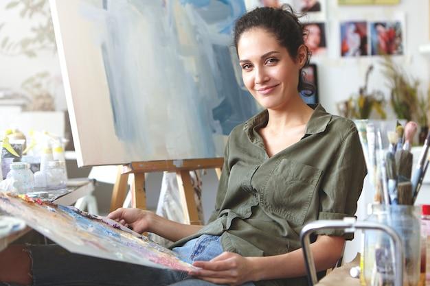 Professionelle künstlerin mit vollständiger beherrschung der farbe und der fertigen technik, die mit aquarellen arbeitet, während sie versucht, eine wunderschöne seelandschaft oder ein ölgemälde zu schaffen. kunst- und hobbykonzept