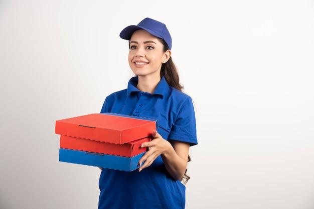 Professionelle lieferfrau, die blaue uniform trägt, liefert pizza. foto in hoher qualität