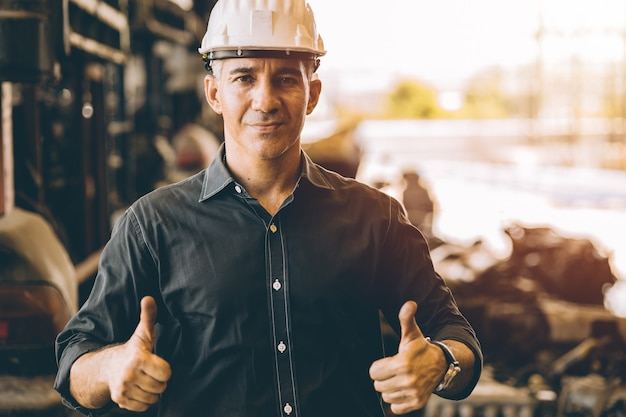 Professionelle männliche arbeit für erwachsene ingenieure in stehenden händen der fabrik zeigen zwei daumen hoch für gute arbeit oder am besten mit selbstbewusstem lächeln