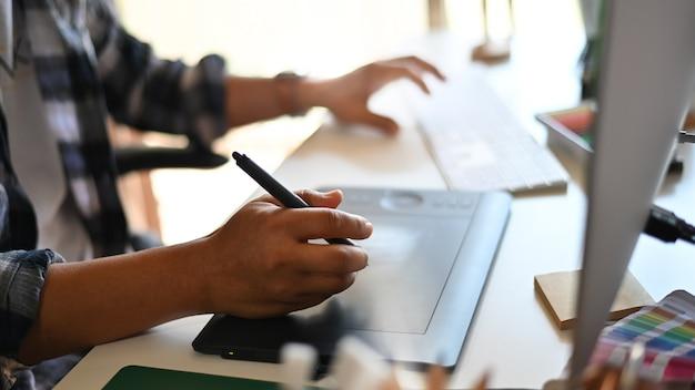 Professionelle männliche freiberuflerzeichnung auf tablette während des neuen projektes mit geerntetem schuss