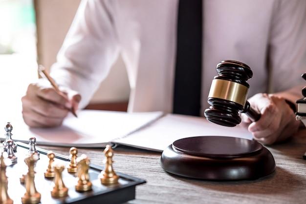 Professionelle männliche rechtsanwälte, die an dem gerichtssaal arbeiten, der am tisch sitzt und papiere mit hammer unterzeichnet