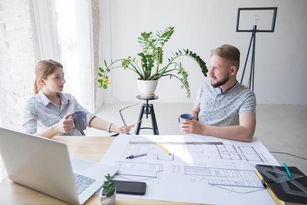 Professionelle männliche und weibliche architektur, die etwas während kaffeepause bespricht