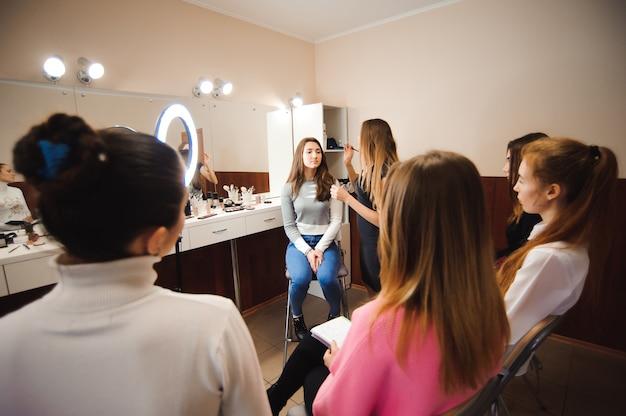 Professionelle make-up-lehrerin, die ihre schülerin zum maskenbildner ausbildet. make-up tutorial lektion in der schönheitsschule. meisterklasse. echte menschen.