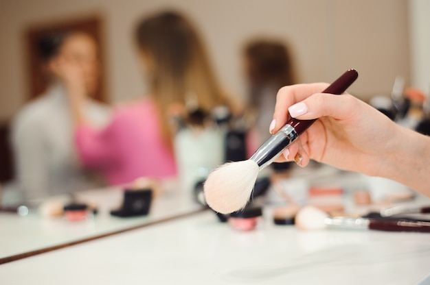 Professionelle make-up pinsel in händen der stylistin