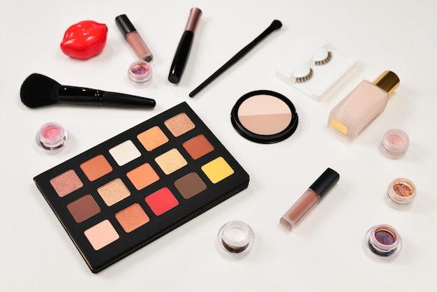 Professionelle make-up-produkte mit kosmetischen schönheitsprodukten, lidschatten, pigmenten, lippenstiften, pinseln und werkzeugen. platz für text oder design.