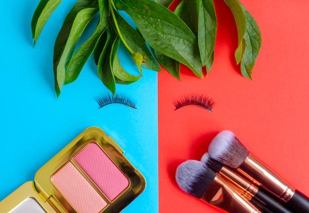Professionelle make-up-werkzeuge lidschatten und pinsel auf einem farbigen blauen und roten hintergrund in form eines gesichts mit falschen wimpern