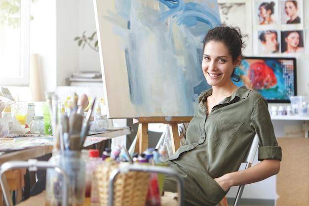 Professionelle malerin, die am stuhl im kunststudio sitzt, hände in den taschen ihres hemdes hält, sanft lächelt, während sie sich nach dem zeichnen des bildes mit aquarellen ausruht. menschen, hobby, malkonzept