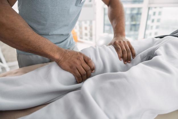 Professionelle massage. schließen sie oben von den männlichen händen, die das bein des patienten während einer professionellen massage berühren