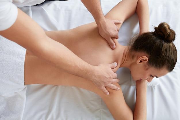 Professionelle massagetherapeutin behandelt eine patientin in der wohnung.