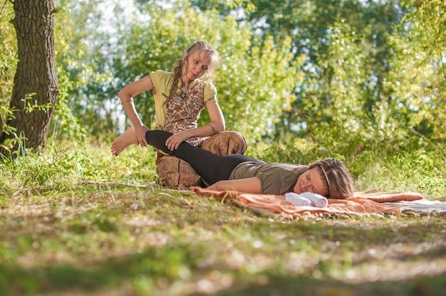 Professionelle masseurin demonstriert erfrischende massagemethoden im wald.