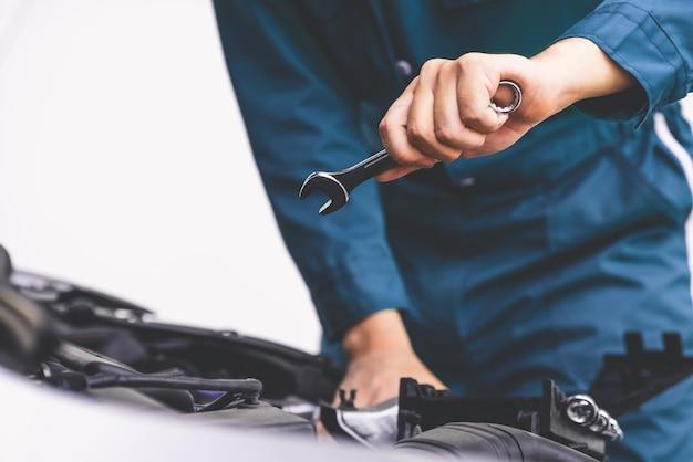 Professionelle mechanikerhand, die autoreparatur- und wartungsservice anbietet