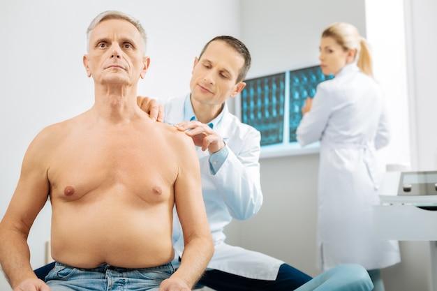 Professionelle medizin. kluger hübscher männlicher therapeut, der die schulter des patienten betrachtet und sie während der arbeit in seinem büro überprüft