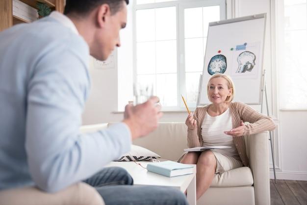 Professionelle meinung. erfolgreicher reifer psychologe, der notizbuch benutzt und mann hilft