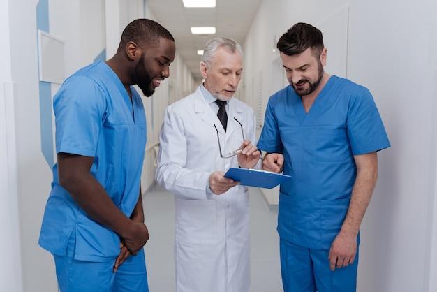 Professionelle meinungen teilen. freundlicher, kompetenter älterer kinderarzt, der im krankenhaus steht, den ordner hält und junge kollegen unterrichtet