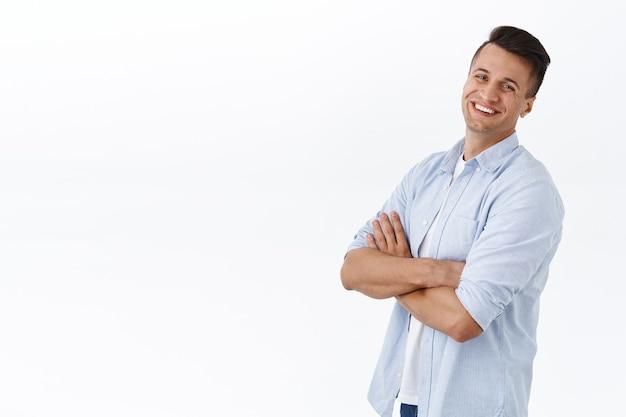 Professionelle menschen, geschäfts- und lifestyle-konzept. porträt eines gutaussehenden, sorglosen erwachsenen mannes, der die brust mit den armen kreuzt, das profil steht und sich mit strahlendem lächeln dreht