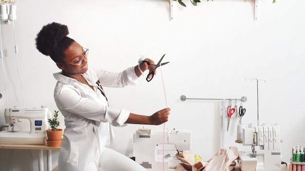 Professionelle modedesignerin der afroamerikanerin, die an stoff in einer werkstatt arbeitet