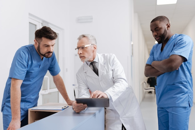Professionelle momente besprechen. hilfreiche optimistische leitende praktikerin, die in der klinik arbeitet und tablets verwendet, während sie sich mit jungen kollegen unterhält