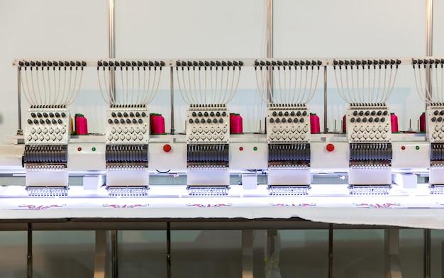 Professionelle nähmaschine bei der arbeit an textilgewebe, niemand. fabrikproduktion, nähherstellung, handarbeitstechnik